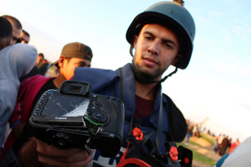 Journalist wearing helmet and flak jacket displays a badly damaged camera