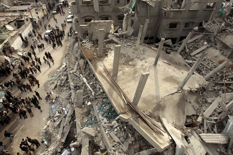 People stand next to the rubble of a mosque in Jabaliya refugee camp. The mosque was destroyed in a missile strike during Israel's 2008-09 war on Gaza