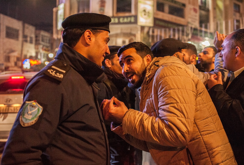 A demonstrator protesting a new Palestinian social security law remonstrates with a policeman in Ramallah.