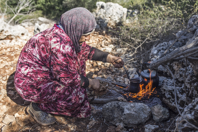 A woman prepares coffee over an open fire.