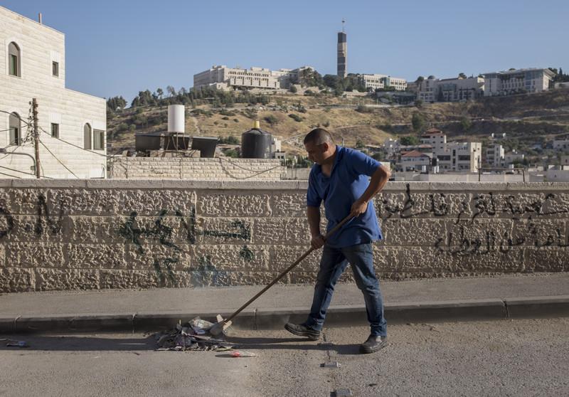 A shopkeeper sweeps the street in Izzawiyeh.