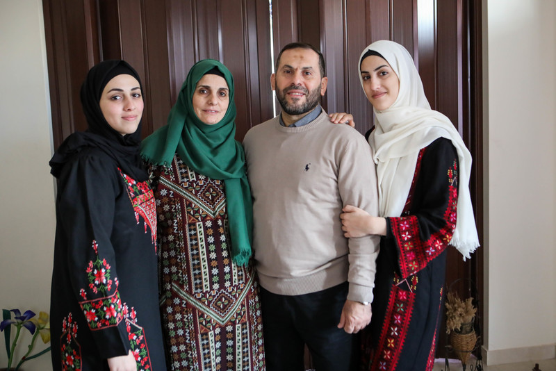 Imad al-Din stands surrounded by his wife and two daughters