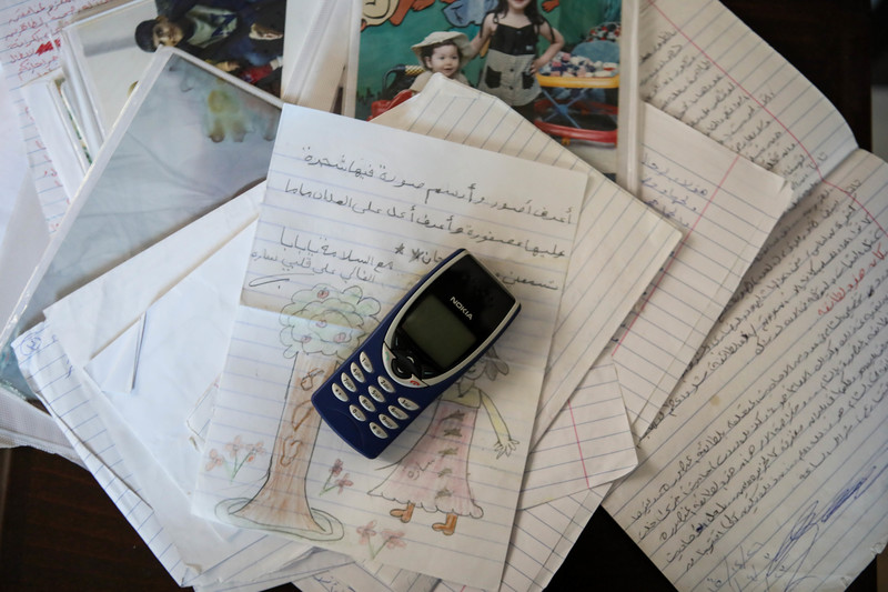 An early model Nokia phone sits on top of a pile of hand-written letters and family photos