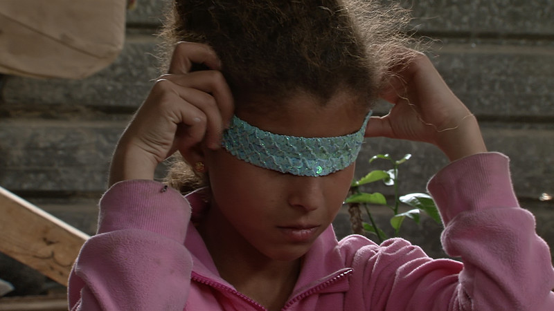 A young girl wraps a sequinned headband over her eyes