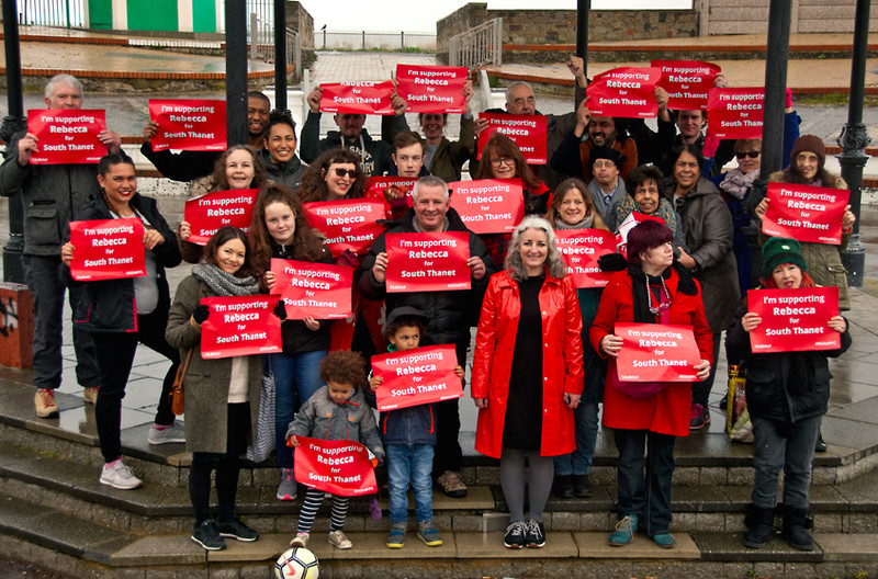 A group of Labour activists hold red signs in support of their prospective candidate for Member of Parliament.