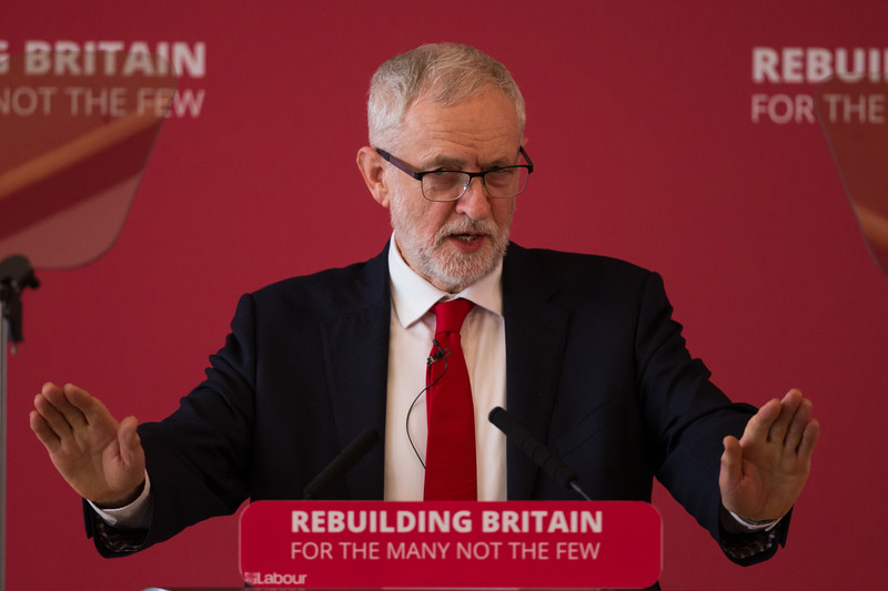 UK opposition leader Jeremy Corbyn standing at a lectern holding his hands up.