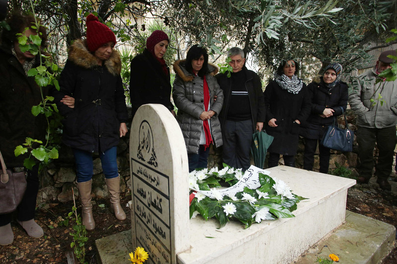 Khalida Jarrar stands near her father's tombstone with others.