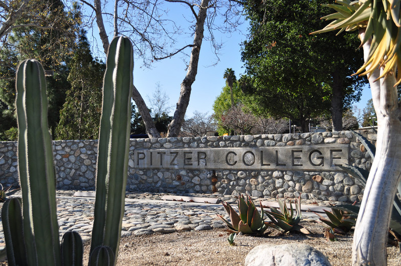 A rock wall displays the name of Pitzer College