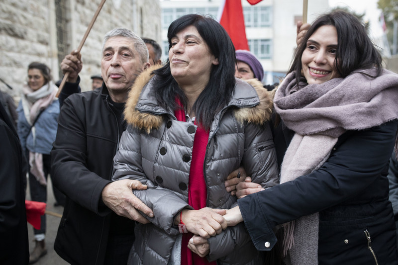 Flanked by her husband and daughter, Khalida Jarrar smiles as she and wellsihers celebrate her release