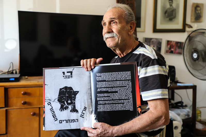 """Black Panther founder Reuven Abergel sits with a book open on a page displaying the logo: """"Enough with poverty!"""""""