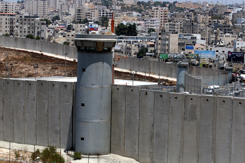 An Israeli watchtower looms over Palestinian houses in the occupied West Bank