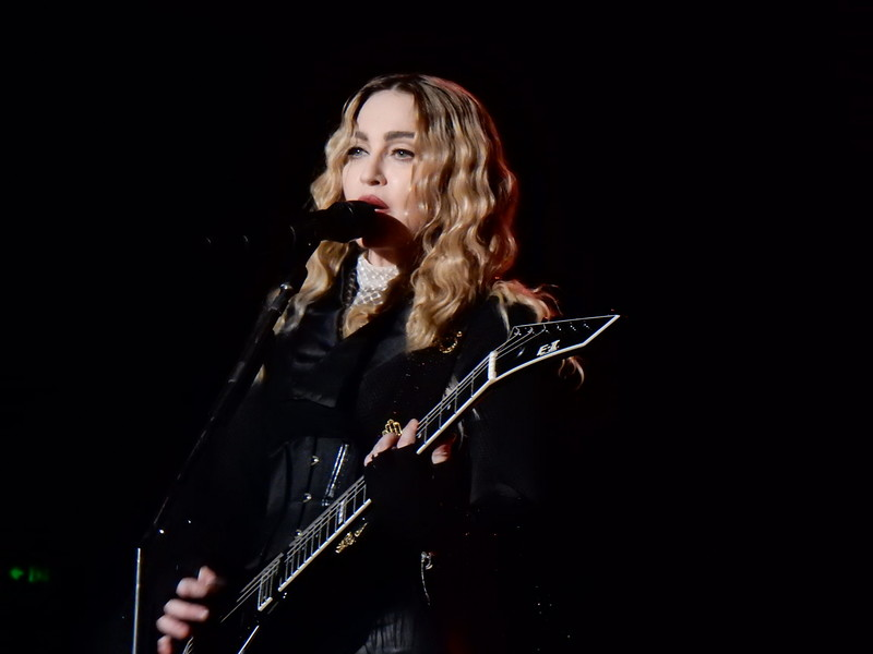 Madonna holding guitar, singing behind a microphone against black background.