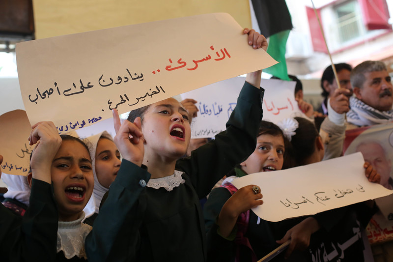 Palestinian children, adults hold banners.
