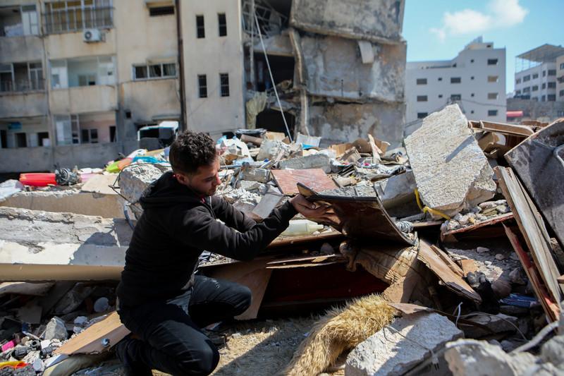 Man combs through rubble