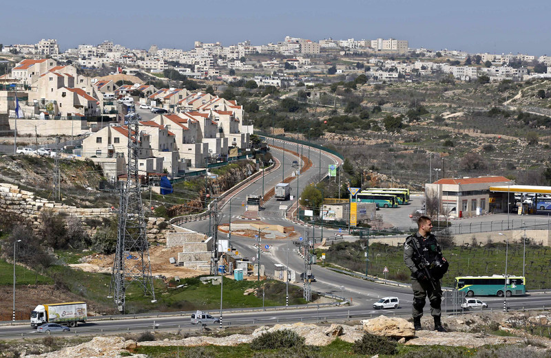 An Israeli soldier stands in front of the entrance to a Jewish-only settlement