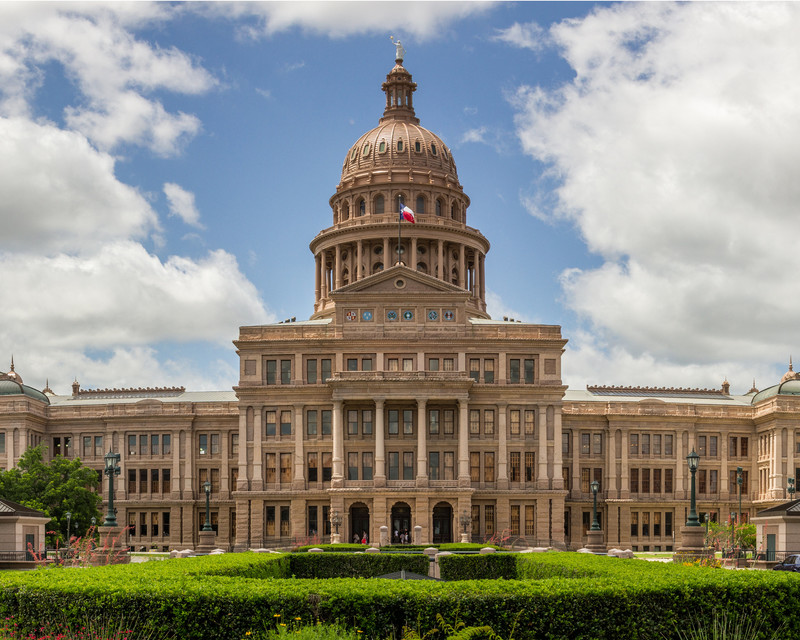The Texas state capitol building with blue sky and clouds in the background.