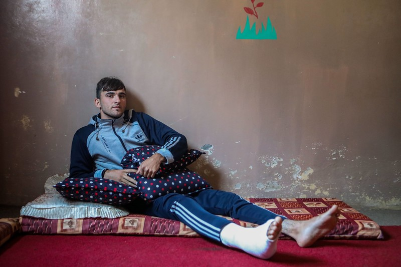 A young man with his right leg in a cast sits on a mattress in front of a bare wall