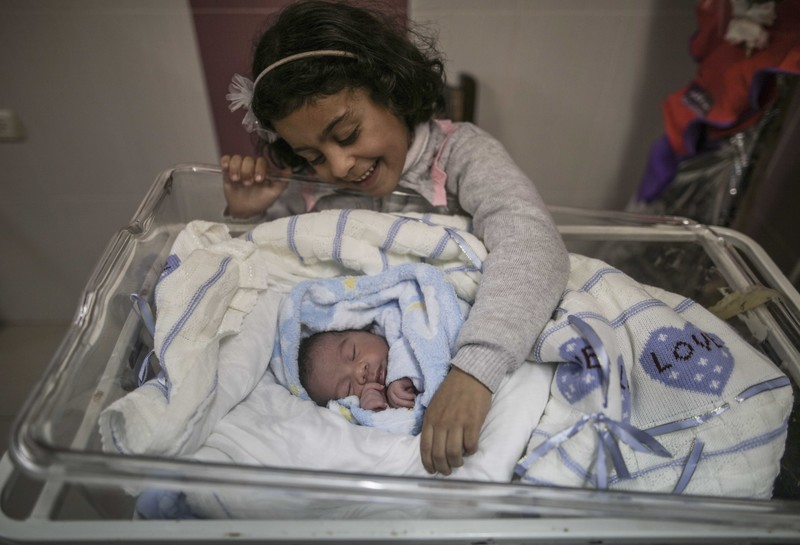 A little girl smiles at a newborn baby wrapped in a blanket.