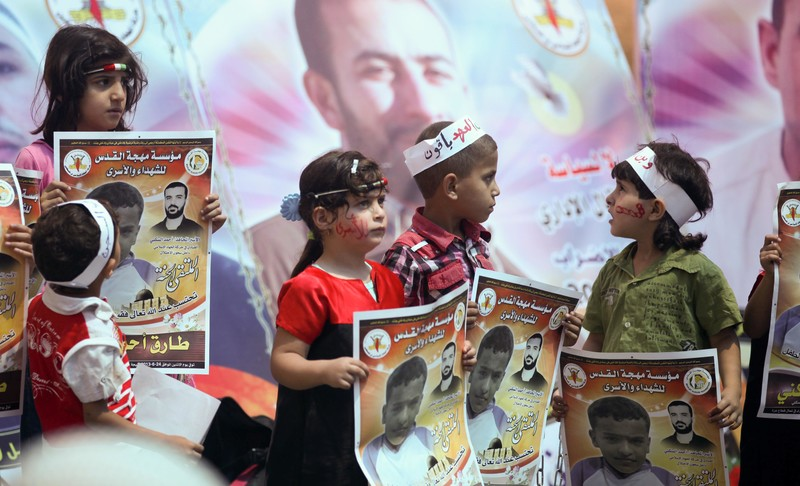 Four children wearing headbands hold up posters depicting a child and bearing text calling for the release of prisoners