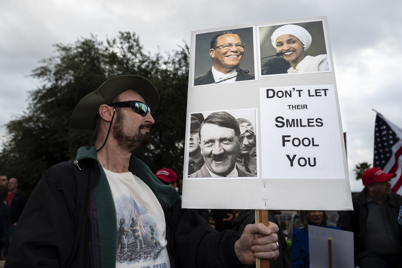 A man holds sign with pictures of Ilhan Omar and Hitler