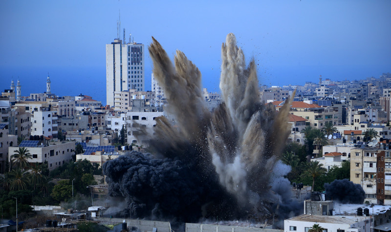 Smoke rises over buildings against Gaza skyline.