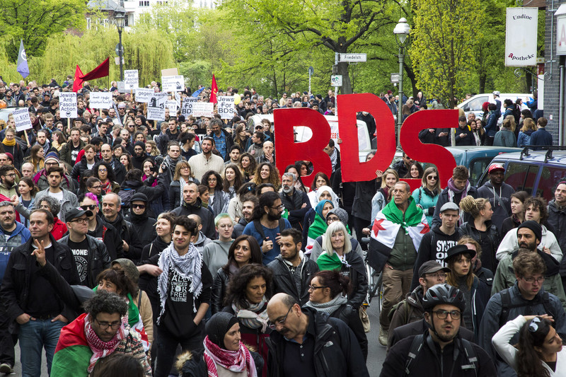 "Hundreds of people march, some with signs that say ""BDS"""