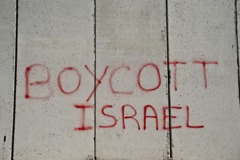 "Graffiti written in red on a grey concrete wall reads, ""Boycott Israel."""
