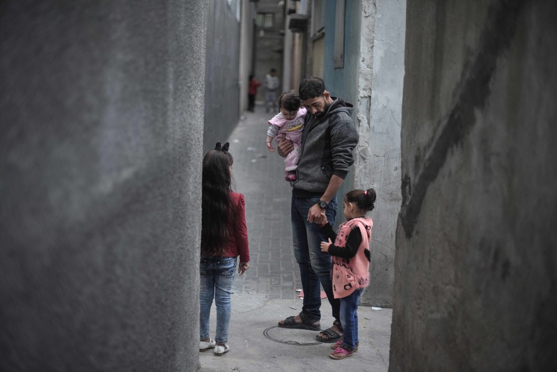 A man carrying a young girl stands flanked by two other children in a narrow grey alley.