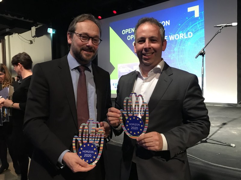 "Two men smile and hold trophies that say ""Horizon 2020"""