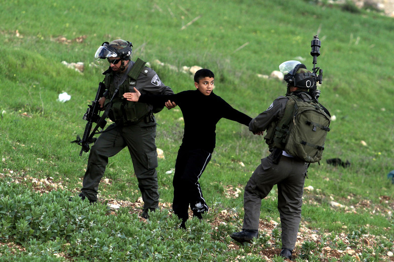 Two Israeli soldiers pull on the arms of a Palestinian youth.
