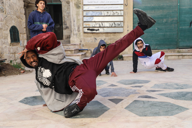 Man does breakdance move surrounded by three onlookers.