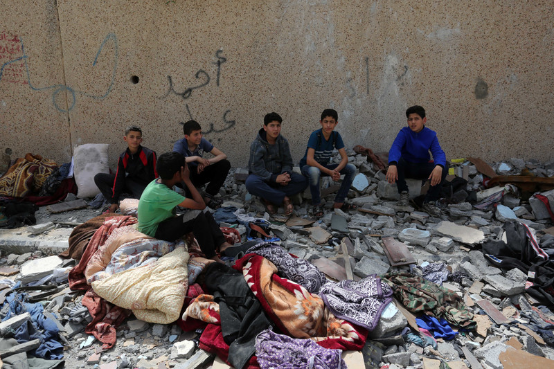 6 boys surrounded by rubble and damaged belongings