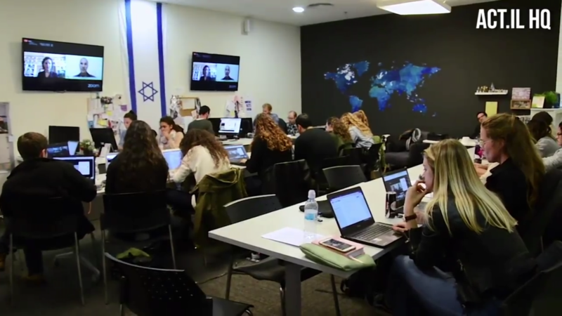 People in a room sit at computers with an Israeli flag on the wall