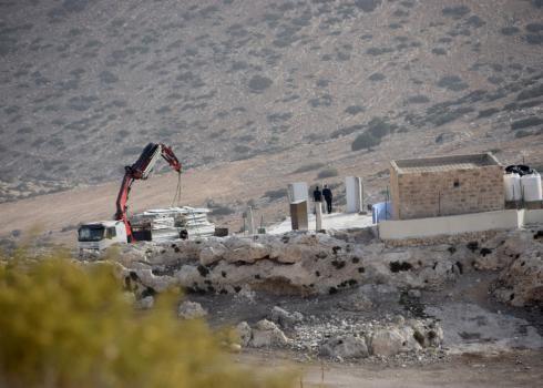 Contruction equipment loads parts of a prefab building