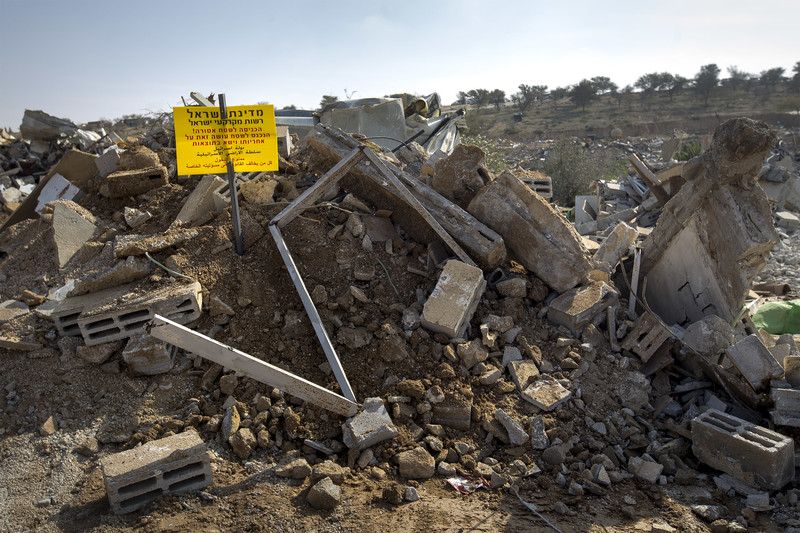 A warning sign in Hebrew and Arabic is posted on pile of rubble
