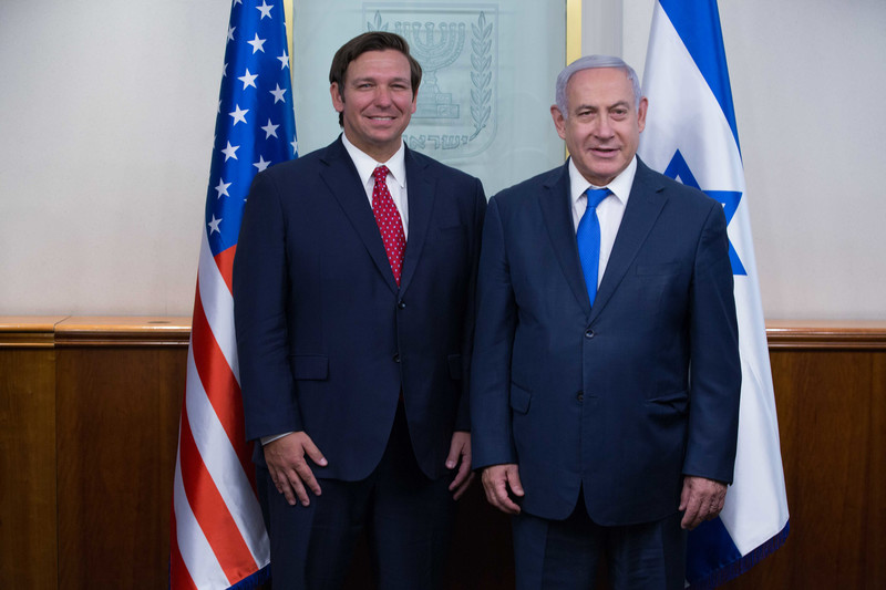 Florida Governor Ron DeSantis stands next to Benjamin Netanyahu, with US and Israel flags behind them.