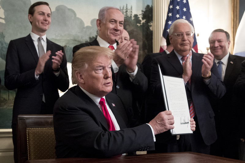 Four standing men applaud another man sat at a desk holding up a piece of paper.