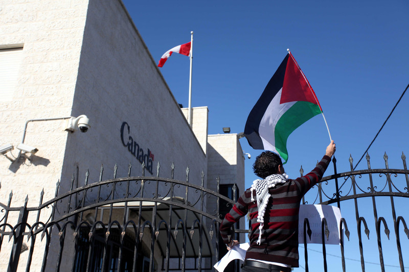 A protester waves a Palestinian flag over the gate of the Canadian embassy in Ramallah.