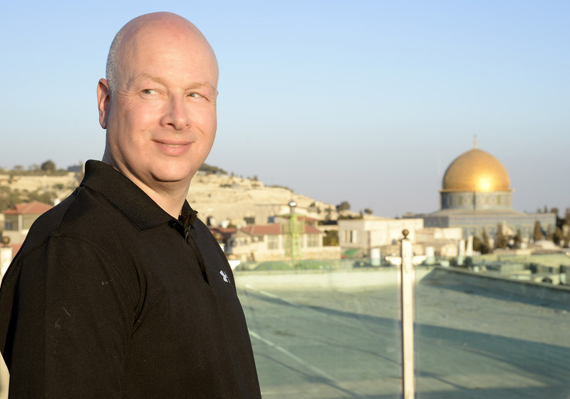 Man smiles with golden dome and other buildings behind him.