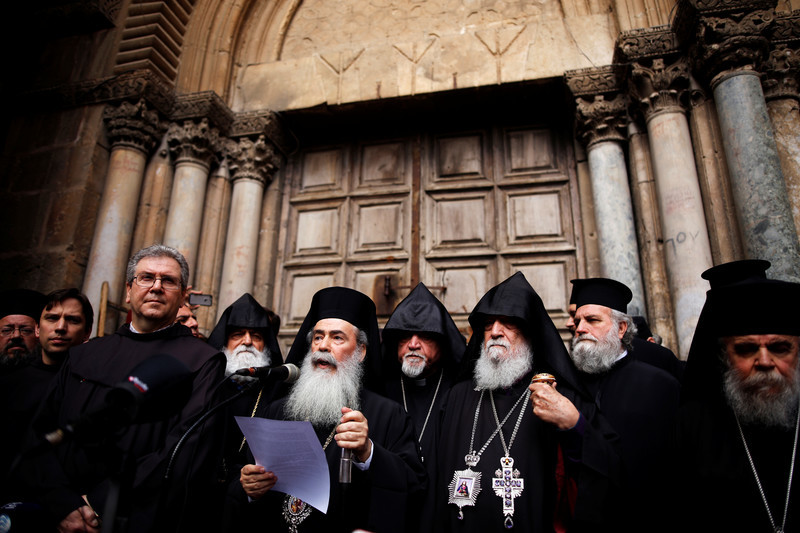 Men dressed in black robes stand side by side