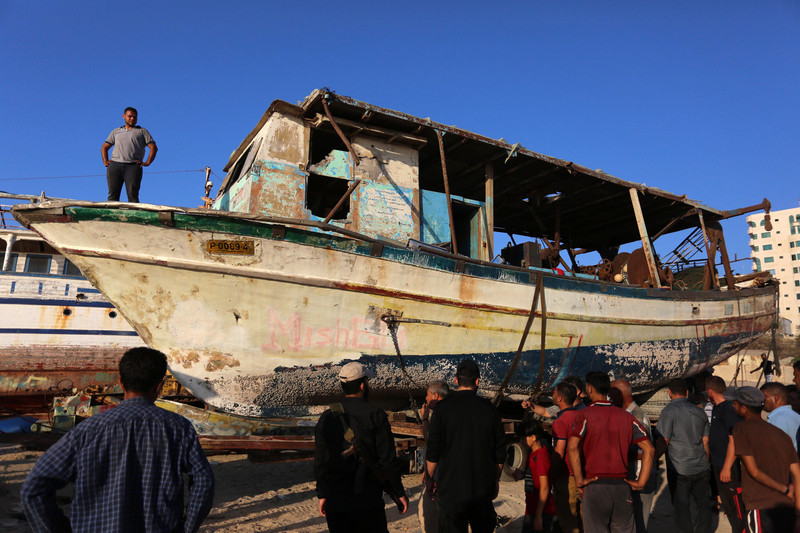 Crowd stands around dilapidated boat