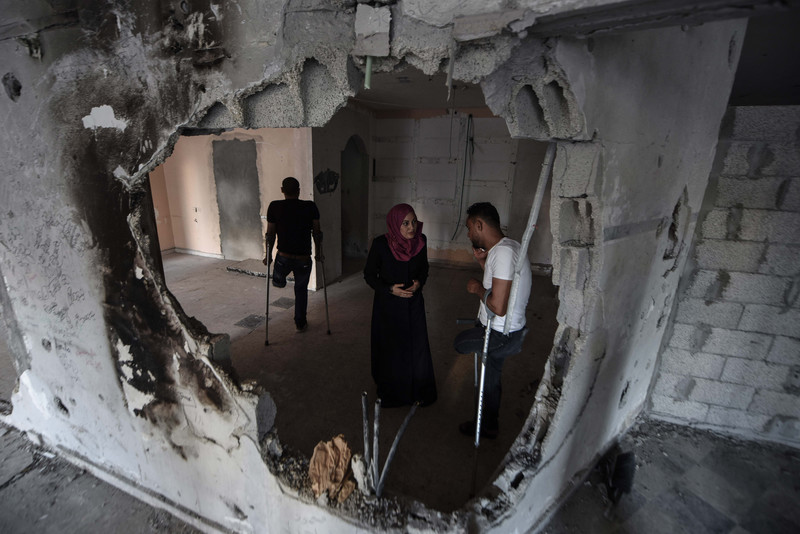 Man and woman stand in front of bombed-out wall