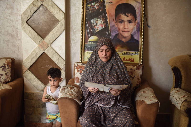 Woman sits in front of poster commemorating killed boy