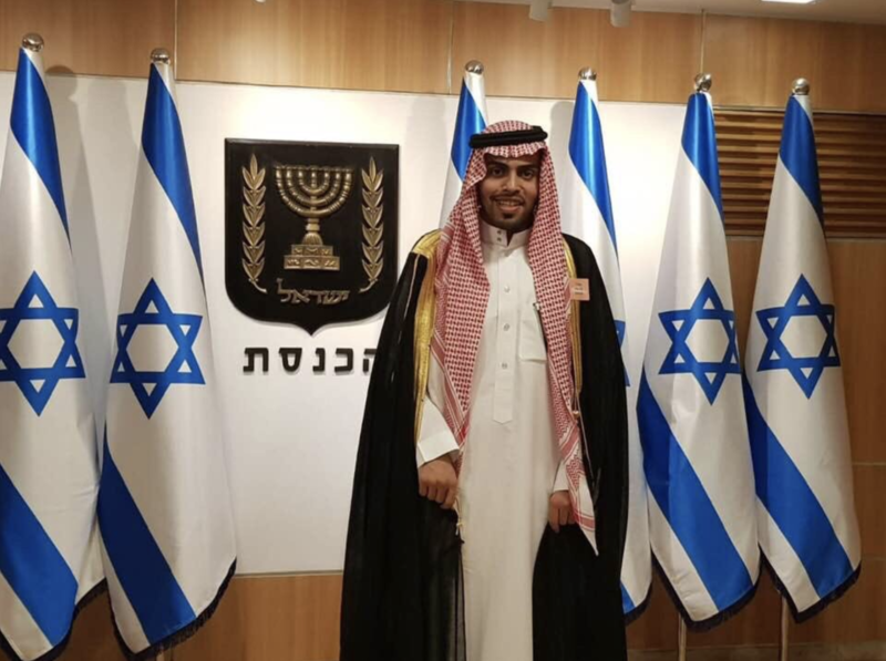Man stands in front of Israeli flags