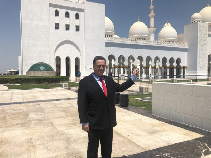Man in suit points to mosque.