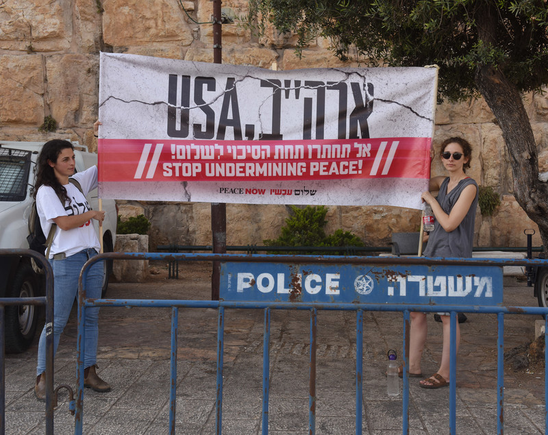 "Two women hold up a sign reading ""USA stop undermining peace"" in English and Hebrew"
