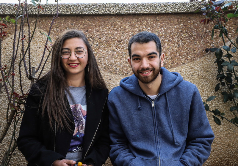 A young man and woman smile at the camera
