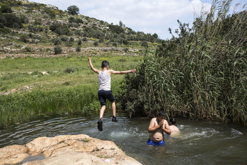 A Palestinian child jumps in a pool
