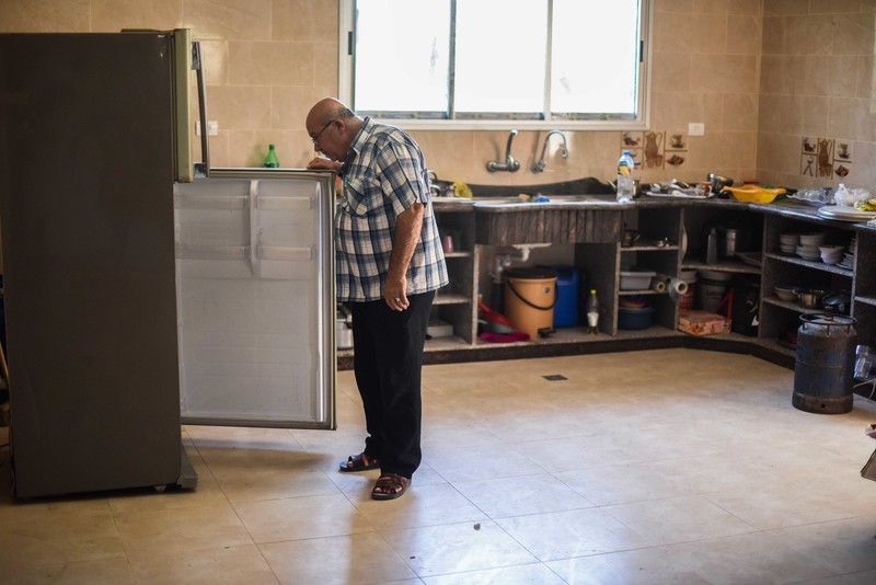 Man opens refrigerator door in spacious kitchen