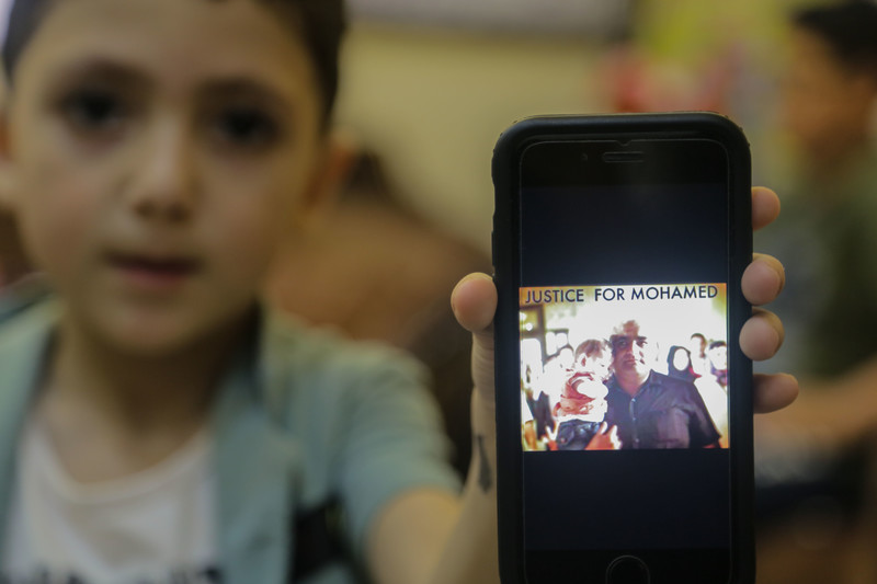 Image: A boy holds a mobile phone with a picture of a man holding a baby Faris, Mohammed el-Halabi's youngest son, holds up a phone with a photo of the last time the two were pictured together, when Faris was just a baby. (Mohammed Al-Hajjar)